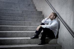 Mann im Business-Look sitzt auf Treppe und hält verzweifelt rechte Hand in seinem Gesicht.