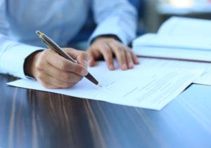Hand unterschreibt mit Kugelschreiber einen Arbeitsvertrag an einem Tisch