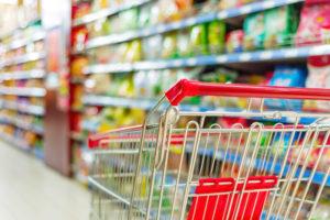 Leerer Einkaufwagen steht vor vollen Supermarktregalen
