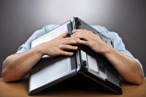 Mann im blauen Hemd liegt mit seinem Kopf auf dem Tisch, auf seinem Kopf liegt ein aufgeklappter Laptop.