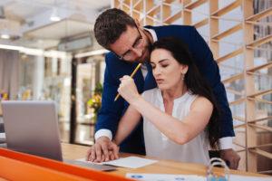 Mann legt am Arbeitsplatz seine Hand auf die einer Frau, die am Schreibtisch mit Laptop sitzt. Sie wehrt sich mit einer Faust, in der sie einen Bleistift hält.