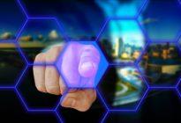 Der Zeigefinger einer Hand zeigt auf einen Blockchain-/Computervordergrund