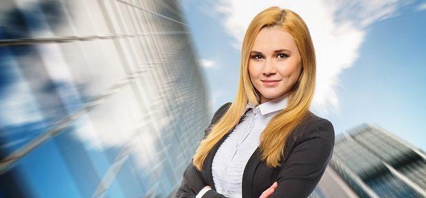 Business Frau mit langen, blonden Haaren steht vor Hochhäusern