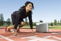 Businessfrau in Startlöchern und in Sprinterposition