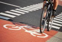 Ein Fahrradfahrer, dessen Beine nur zu sehen sind, fährt auf Radweg