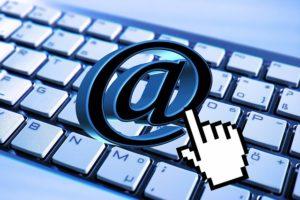 Auf einer Computertastatur liegt ein at-Zeichen, eine kleine Computerhand zeigt darauf