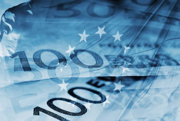 Blaue Eurogeldscheine mit EU-Flagge im Hintergrund