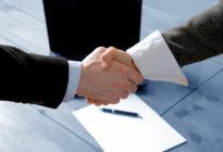 Eine männliche und eine weibliche Hand schütteln sich gegenseitig, unter ihnen liegt ein Papier mit Stift