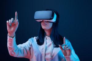 Frau mit Virtual Reality-Brille streckt Finger in die Höhe