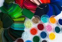In Döschen befinden sich Plastikpolymergranulate in verschiedenen Farben, daneben sind verschiedenfarbige Schlüsselanhänger
