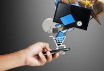 Hand mit Mobiltelefon, auf dem ein Einkaufswagen mit Waren ist