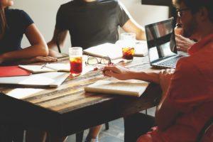 Startup: junge Leute arbeiten am Bürotisch mit Laptop und Blöcken