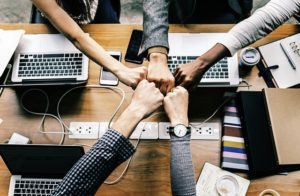 Geballte Hände, die in einem Büro neben ihren Laptops auf dem Schreibtisch aufeinandertreffen und ein Team symbolisieren
