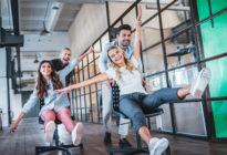 Zwei junge Männer schieben zwei junge Frauen auf Stühlen mit Rollen durch ein Startup-Büro