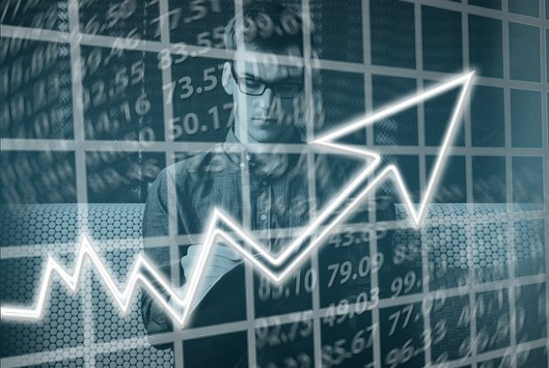 junger Unternehmer schreibt auf einen Block, vor ihm ein steigender Graph für wirtschaftlichen Aufschwung