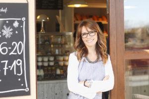 Cafébesitzerin vor ihrem Laden