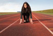 Businessfrau, die sich auf einer Rennstrecke in Startposition befindet