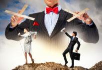 Businessmann hält eine Business-Frau und einen Businessmann als Handpuppen an einem Seil