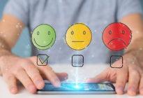 Kundenfeedback mit drei Emojis und Hände auf Smartphone