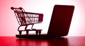 Kleiner Einkaufswagen, der auf Laptop steht
