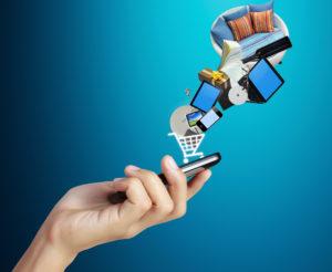 Hand mit Smartphone, auf dem ein Einkaufswagen mit Waren zu sehen ist
