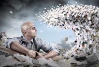 Businessmann, der vor einer Welle von Papier sitzt