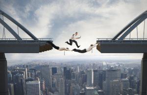 Zwei Businessmänner, die an Brückenteilen hängen, ein Businessmann läuft mit Laptop über die beiden, Symbol für Teamkonzept