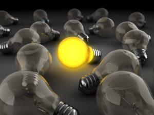 Eine Glühlampe leuchtet hell neben mehreren, nicht leuchtenden Glühlampen