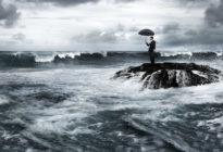 Krise: Business-Mann mit Regenschirm steht auf kleiner Felsen-Insel im reißenden Meer