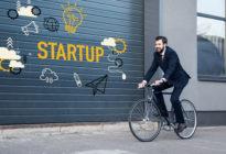 Fahrradfahrer im Business-Look, der an Grarage mit Aufschrift Startup vorbeiradelt