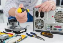 Technikerhänder reparieren Computer mit Schraubenschlüssel
