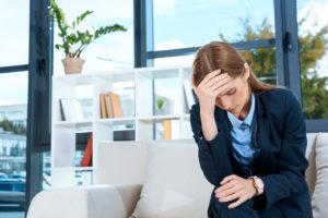 Geschäftsfrau - mit Angst und Depression - hält sich Hand vor ihr Gesicht