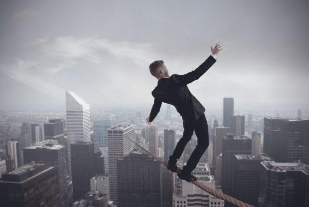 Businessmann balanciert auf Seil über Hochhäuser