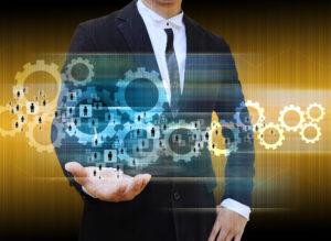 Businessmann mit Zahnrädern und Männchen als Symbol für Recruiting