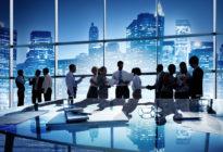 Mehrere Businessleute im Büro vor Skyline