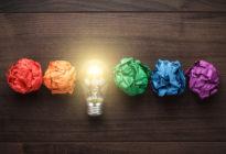 5 farbige Papierkugeln und dazwischen eine Glühlampe