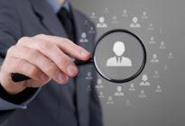 Hand untersucht mit Lupe grafisch dargestellte Personen; Symbol für Recruiting
