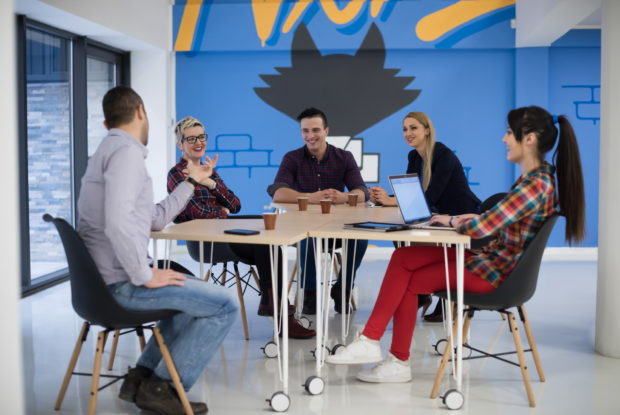 Junge Leute eines Startups im Meeting an Bürotischen und mit Laptops