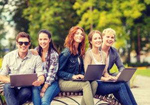 5 junge Leute mit Laptop auf einer Parkbank