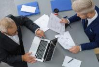Zwei Geschäftsleute analysieren Diagramme in einem Meeting