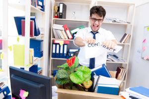 Geschäftsmann, der von seinem Job gefeuert wurde, zerreisst im Büro ein Zettel mit Aufschrift Contract