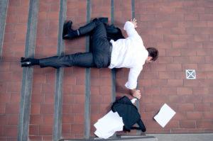 Businessmann fällt auf Treppe hin und verliert Aktentasche mit Papieren
