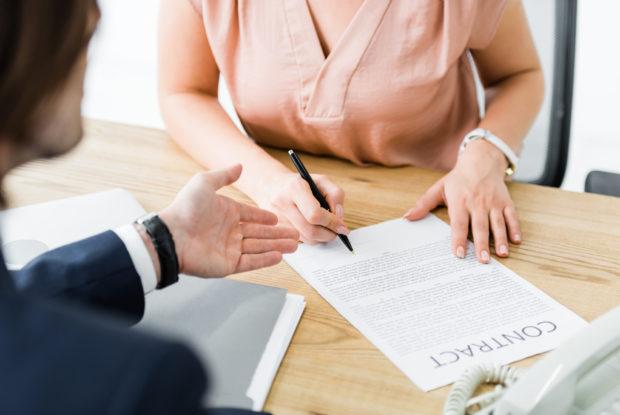 Geschäftsfrau unterzeichnet neben ihrem Chef einen Vertrag