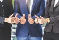 Drei Businessmänner halten die Daumen hoch