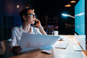 Junge Frau sitzt vor einem Computer und einer Zeichnung