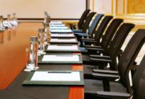 Besprechungsraum mit Tischen, auf denen Wasser und Blöcke stehen und leeren Stühlen