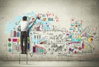 Junger Mann zeichnet auf Wand Start-up Strategie
