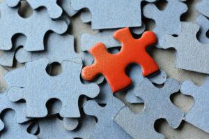 Mehrere blaue und ein rotes Puzzleteil