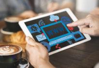 Hände halten Tablet mit Bild von einem Computerbildschirm und der Aufschrift www.