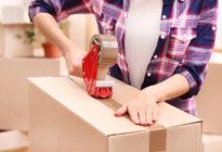 Hände packen mit Klebeband Kartons